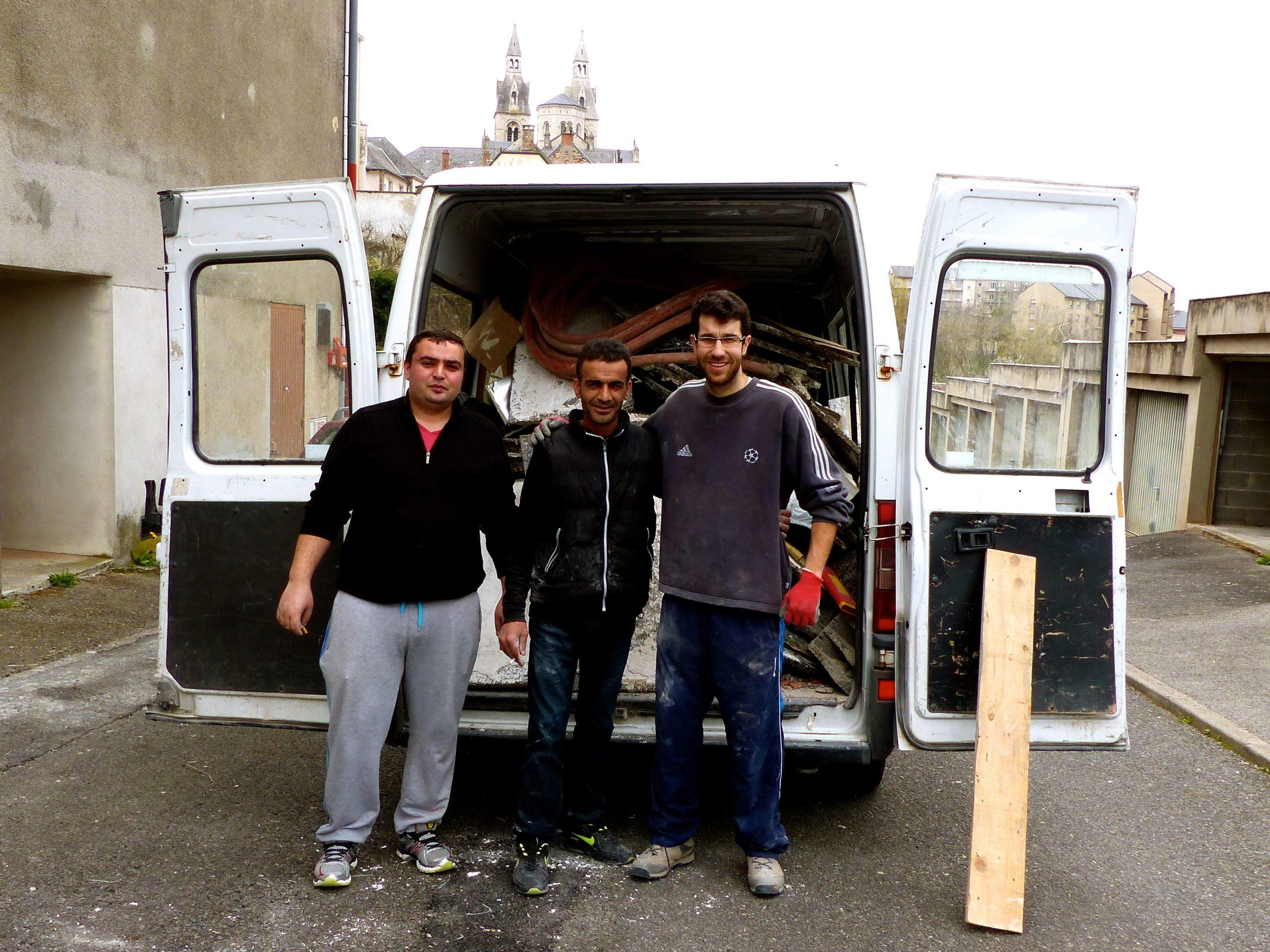 Trois hommes souriants devant un camion à une déchèterie